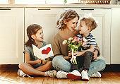Little children congratulating mother in kitchen