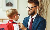 Happy father adjusting garment of schoolkid