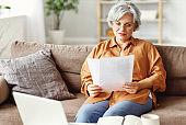 Happy elderly freelancer reading papers on sofa