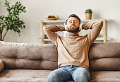 Young man with headphones resting on sofa