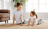 Happy mother and daughter exercising together at home