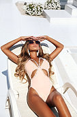 sensual woman with blond hair in elegant swimming suit relaxing in luxurious white villa