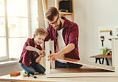 Happy father and son assembling furniture on table