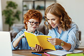 Mother helping child with homework, looks at her son's notebook at home