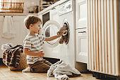 happy  householder child boy in laundry   with washing machine