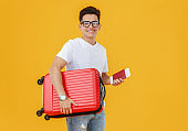 Cheerful male traveler with suitcase