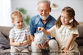 Grandfather helping grandchildren to save money