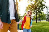 Cheerful schoolgirl walking to school with father