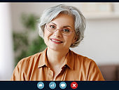 Happy elderly woman sit at home talk on video call with relatives,