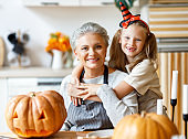 Happy granddaughter and grandmother preparing for Halloween celebration