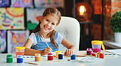 funny child girl draws laughing   with paint