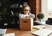 Happy woman with carton box at table in loft office