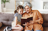Cheerful grandmother and granddaughter reading book together