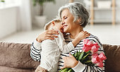 Cheerful little boy giving flowers to grandmother
