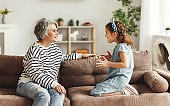 Girl speaking and sharing secret with grandmother