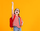 Happy schoolgirl in glasses celebrating success