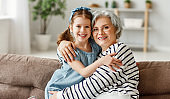 Happy senior woman hug granddaughter