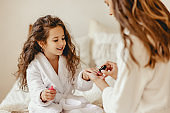 happy family mother and little daughter in bathrobe makes manicure, laugh  on Spa day at home