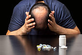 depressed bald man next to a lot of pills