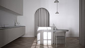Luxury elegant kitchen in classic room with stucco molded walls and parquet floor. Arched panoramic window, island with chairs, vase, candles and decors. White interior design