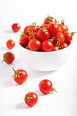 red cherry tomato in  ceramic bowl on white background