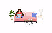 Girls working at home. Young woman sitting on a sofa and using laptop. Freelance, self employed, freedom, in living room.