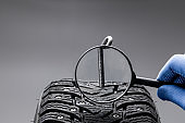 huge nail on a tyre over black background. studio shot. copy space. repair car tire concept. trouble on path conceptual
