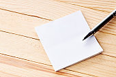 office workplace with blank sticky note. above view. wooden desk. background backdrop