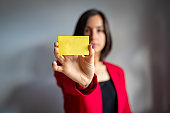 Young business woman with red blazer showing adhesive note from kanban board