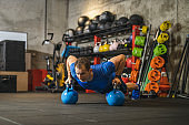 Determined athlete doing push-ups on kettlebells in gym