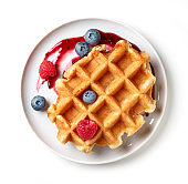 dessert of belgian waffle and fresh berries isolated on white