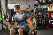 Muscular guy in sportswear lifting dumbbell while sitting on bench at cross training gym. Mature athlete using dumbbell during a workout. Strong man under physical exertion pumping up bicep muscle with heavy weight.