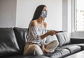 Young woman relaxing on the sofa and watching tv during pandemic of coronavirus