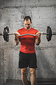 Mid adult muscular guy in sportswear lifting dumbbell