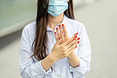 Woman using antibacterial hand sanitizer on hands
