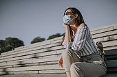 Portrait of woman with medical face mask sitting on stairs during pandemic of coronavirus