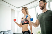 Fit young couple doing home workout with dumbbells