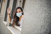 Young adult woman leaning to an opened window, looking outside through it and waving to the neighbors, while relaxing at home during quarantine because of coronavirus
