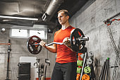 Mid adult muscular guy in sportswear lifting dumbbell  at cross training gym. Mature athlete using dumbbell during a workout. Strong man under physical exertion pumping up triceps muscle with heavy weight.
