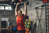 Portrait of athlete doing exercise for triceps with dumbbells