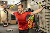 Man performing training in gym. Muscular guy doing exercise with elastic rope