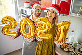 Beautiful couple preparing for party, decorating home and preparing food for Christmas or New Year at home