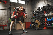Caucasian bodybuilder with serious facial expression working out with Bulgarian Training bag