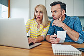 Shocked couple looking at laptop while managing home finances