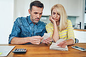 Sad couple looking at store receipt while managing home finances worried about money