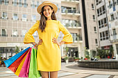 Happy fashionable woman with colorful shopping bags wearing hat and yellow dress and enjoying in shopping mall
