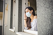 Young adult woman leaning to an opened window, looking outside through it, having headache and wearing medical face mask during quarantine because of coronavirus