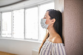 Nervous young woman having anxiety attack during pandemic of coronavirus at home