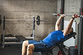 Sports man doing bench press, athlete during training in professional gym, lifting weights for biceps, pectorals and back muscles