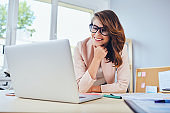 Smiling woman looking on laptop while working in small office or home office